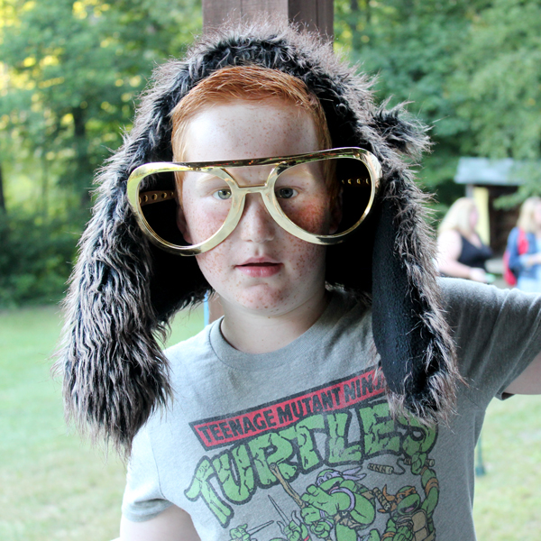 Red haired camper wearing outsized glasses and furry wig at Camp Can Do, Gretna Glen, PA